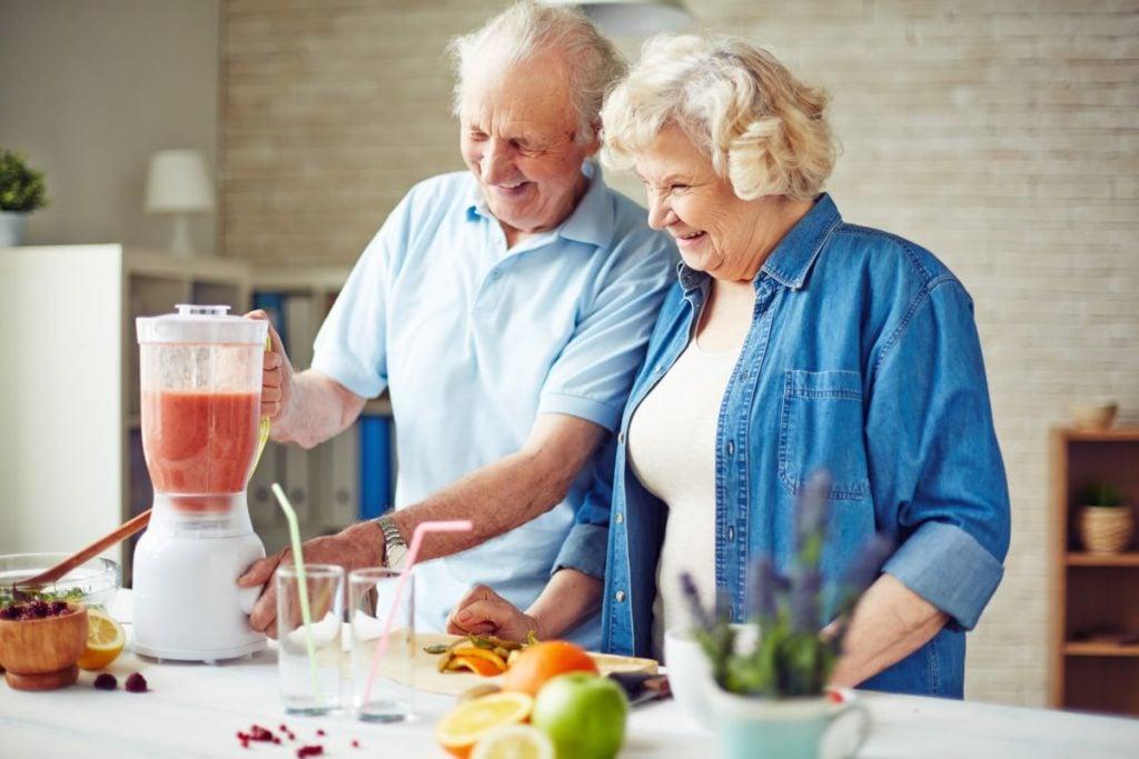 senior couple making fruit smoothie