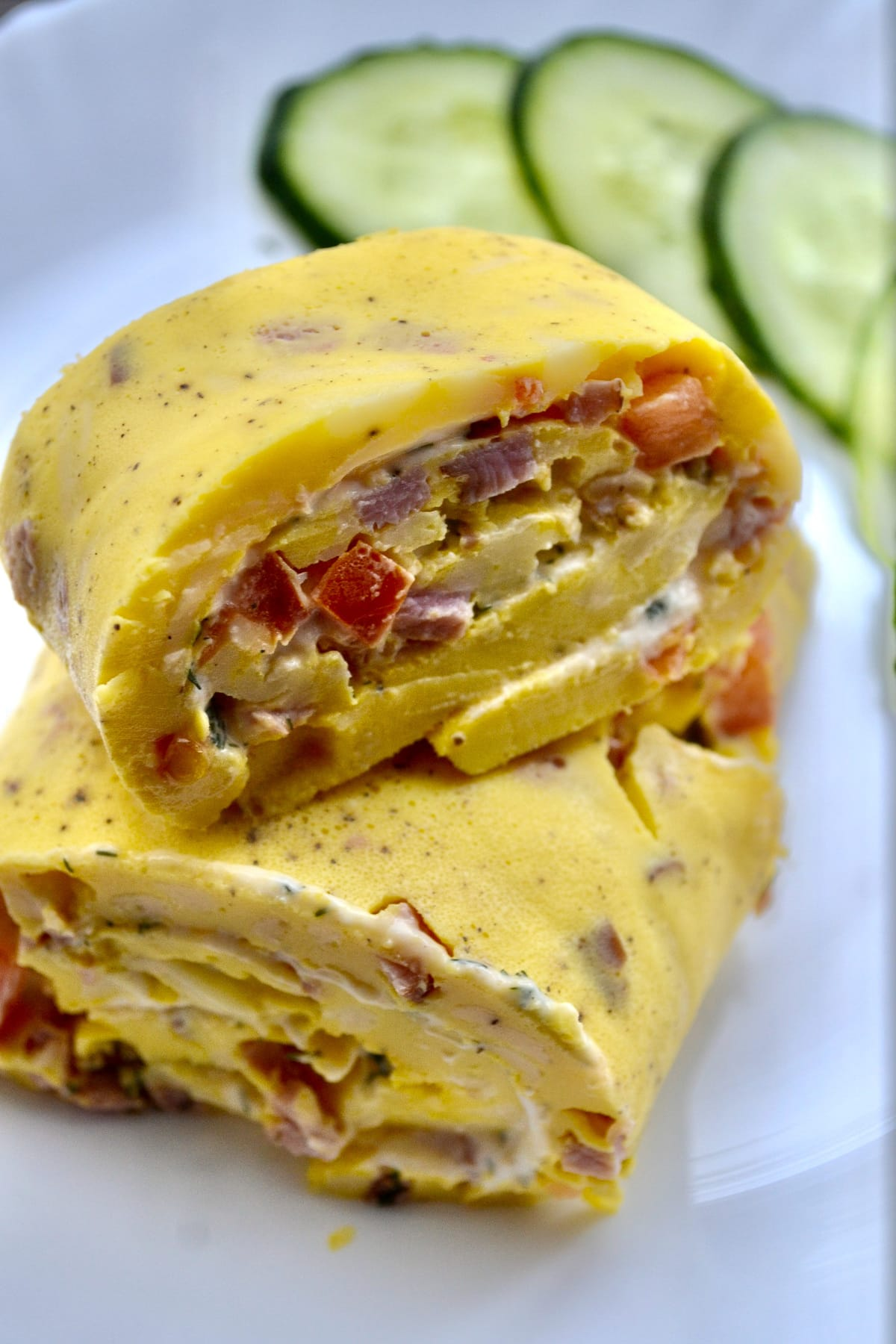 Keto baked omelet roll with cucumbers on side