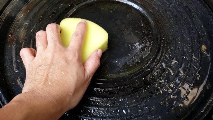 Cleaning sponge scrubbing bottom of cast iron frying pan