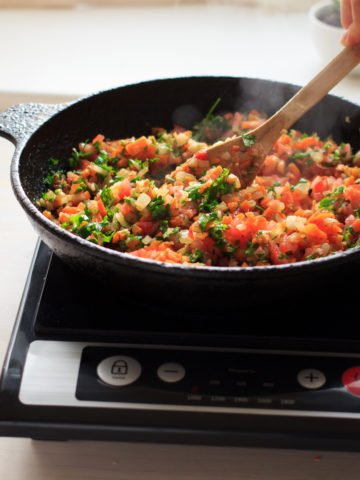 Induction cooking at home on a black portable cooker in cast iron cookware