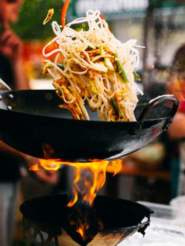 man cooks noodles using a wok